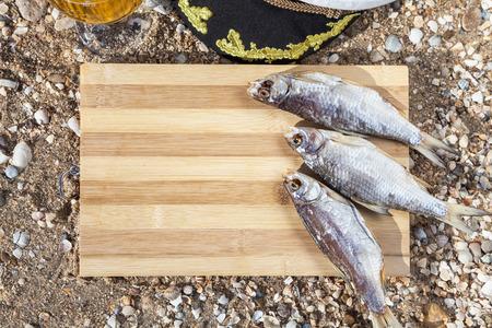 culinary: Marine culinary still life with beer, fish and marine cap Stock Photo