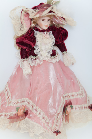 cuffs: Doll lady in elegant velvet dress with a hat on white background