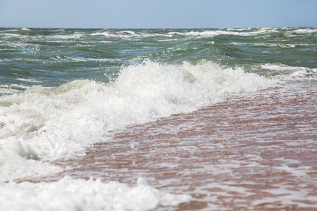 rages: Sea wave on a sandy beach at summer morning Stock Photo