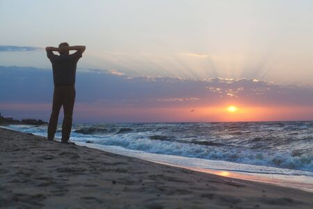 come up: Man stands on the beach and watching sun come up through the clouds on the sea horizon