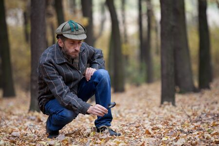 considers: Man detective with a beard wearing a cap and plaid jacket considers through magnifying glass trail in autumn forest
