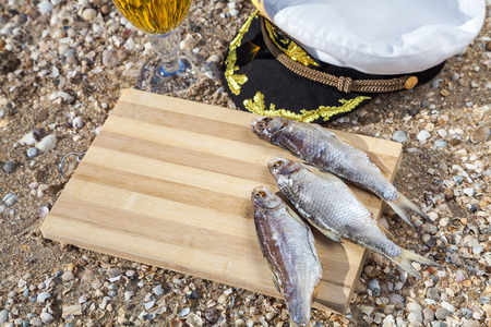 culinary tourism: Marine culinary still life with beer, fish and marine cap Stock Photo