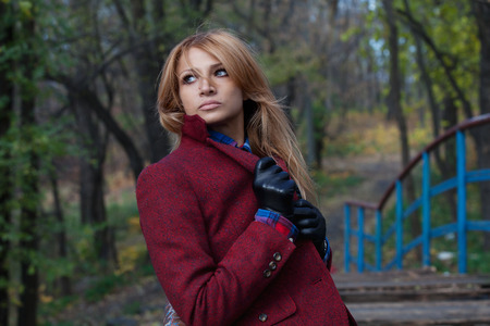 short gloves: Beautiful thoughtful blonde woman in jacket and leather gloves leaning against handrail
