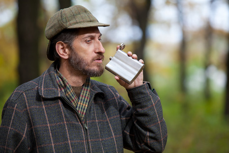 brings: Man with a beard wearing cap and plaid jacket brings to mouth metal flask in autumn forest Stock Photo