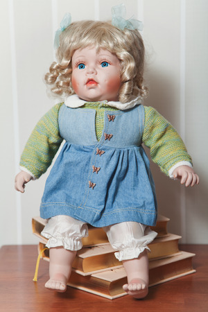 Vintage porcelain doll blonde with blue ribbons sitting on stack of books Stockfoto
