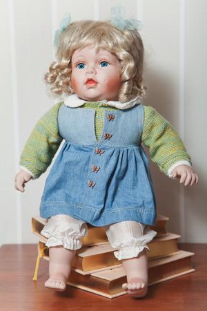 Vintage porcelain doll blonde with blue ribbons sitting on stack of books Standard-Bild