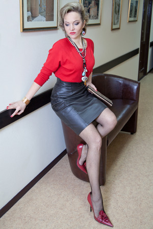 faldas: Hermosa rubia mujer en longitud completa en el suéter rojo plantea contra una pared con fotos Foto de archivo