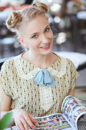 fashion magazine: Portrait of beautiful blonde girl in romantic retro dress with fashion magazine at street cafe