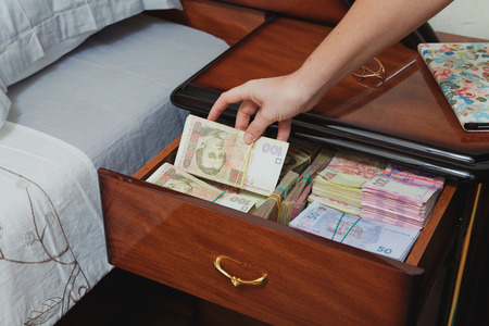 Hand pulls out wad of money from the bedside table filled with Ukrainian cash Stock Photo