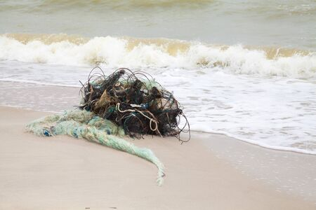 ichthyology: Tangled remains of fishing nets thrown wave on the sea shore