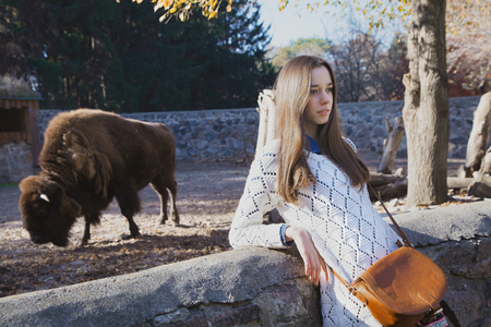 aviary: Young beautiful girl stands near the aviary with bison in city zoo on sunny autumn day