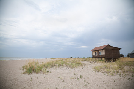 secluded: Secluded wooden house on sea beach on a cloudy day