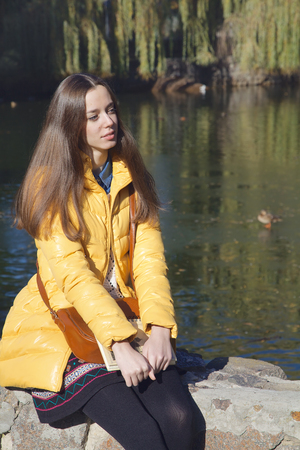 Beautiful thoughtful girl-student sits on parapet near the city pond in sunny autumn day