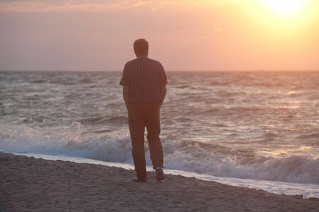 come up to: Man walking on the beach and watching sun come up through the clouds on the sea horizon