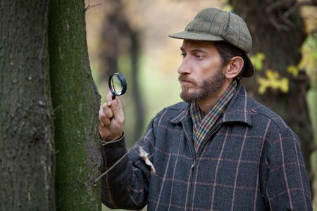 considers: Man detective with beard wearing cap and plaid jacket considers through magnifying glass tree in autumn forest