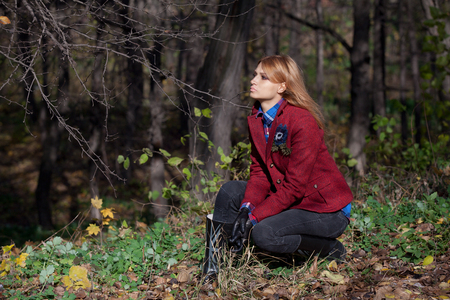 rubber: Pretty woman with flowing hair in tweed jacket and leather gloves sitting at grass in autumn forest