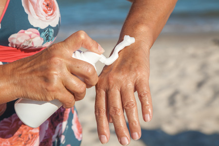 weather protection: Elderly woman in swimsuit smears her hands with sunscreen from a container on the summer sea beach