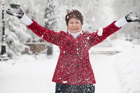 Attractive elderly woman in red coat throws up snow on winter snowy street