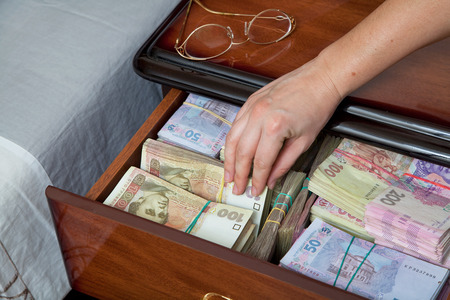 'bedside table': Hand pulls out banknote and wad of money from the bedside table filled with Ukrainian cash Stock Photo