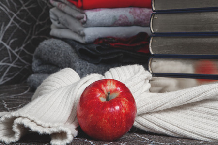 evenings: Composition of reading and relaxation at winter evenings. Stack of books with glossy edge wrapped in warm scarf and red apple foreground