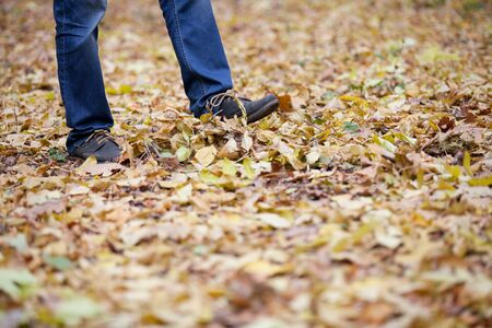 strew: Man in blue jeans walking on fallen leaves