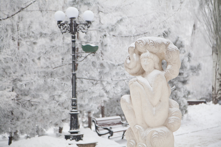 Snow-covered sculpture of sitting girl on a winter city boulevard Stock Photo