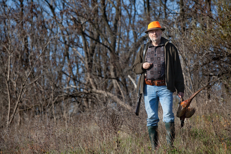 wildfowl: Elderly successful hunter with wildfowl in orange hat Stock Photo