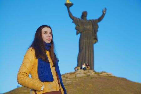 national colors: Young girl dressed in Ukrainian national colors standing on the background of monument to liberators and looking thoughtfully at the autumn blue sky