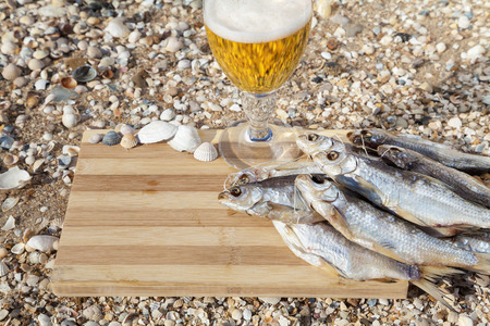 culinary tourism: Bunch of dried fish on a wooden board next to a glass of beer
