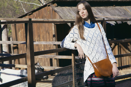 aviary: Young beautiful girl stands near the aviary with lamb in city zoo on sunny autumn day Stock Photo