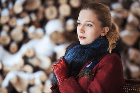 firewood background: Gentlewoman sitting on a bench in winter veranda on firewood background