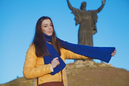 national colors: Young girl dressed in Ukrainian national colors standing on the blue sky background of monument to liberators and holding a blue scarf at autumn sunny day
