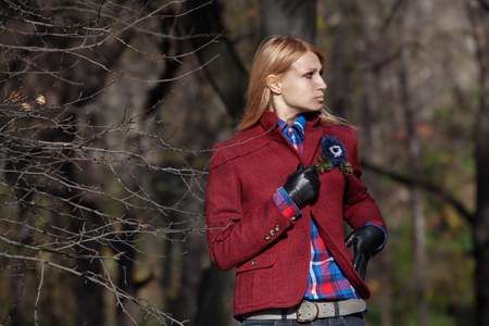 tweed: Pretty woman with flowing hair in tweed jacket and leather gloves walking and posing in autumn forest Stock Photo