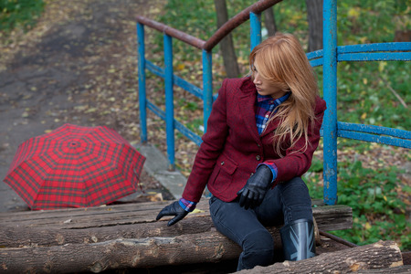 short gloves: Pretty woman with flowing hair in tweed jacket and leather gloves sits on the old bridge in autumn forest Stock Photo