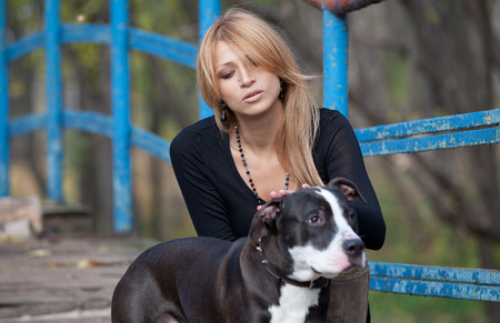 stroking: Glamorous pretty woman with long hair stroking thoroughbred dog on the bridge