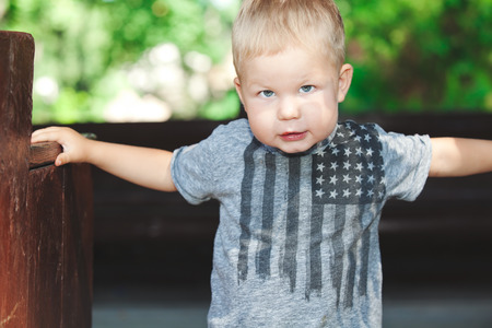 considerate: Blond little boy in gray t-shirt seriously looking into camera on walking summer day