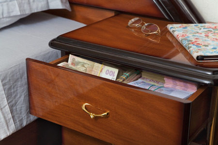 stingy: Bundles of banknotes in bedside table filled with Ukrainian cash