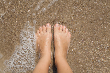beach feet: Two female bare feet on wet sand in the sea foam Stock Photo