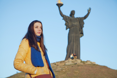 national colors: Young girl dressed in Ukrainian national colors standing on the background of monument to liberators and thinks about the fate of the motherland at autumn sunny day Stock Photo