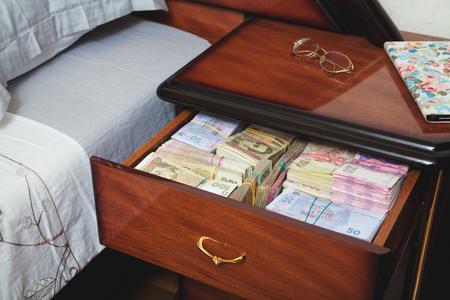 bedside table: Bundles of banknotes in bedside table filled with Ukrainian cash