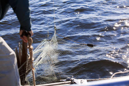 tries: Man tries to free the anchor from fishing net Stock Photo