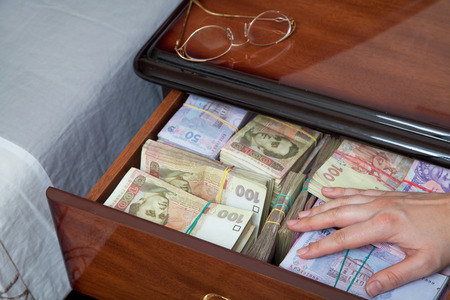 stingy: Hand on the money in bedside table filled with Ukrainian cash Stock Photo