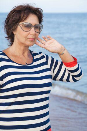 mujer mirando el horizonte: Mujer mayor bonita en gafas de sol de vacaciones en la playa Foto de archivo