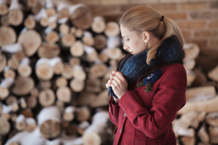firewood background: Gentlewoman in profile standing in winter veranda on firewood background
