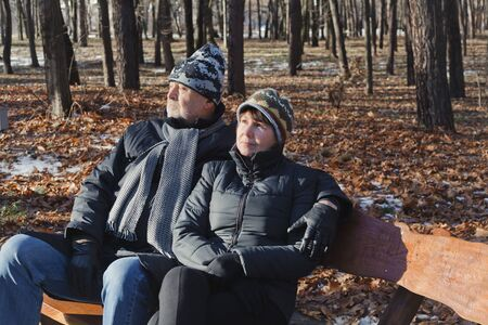 respite: Elderly couple relaxing on a bench in pine forest at early spring