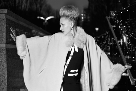 pushes: Elegant blond woman in retro style posing in profile on the street in the evening autumn