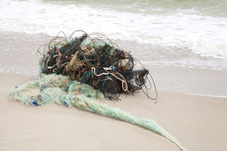 disturbance: Tangled remains of fishing nets thrown wave on the sea shore