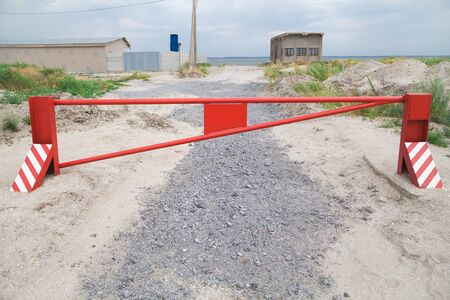 guard rail: Red metal barrier blocking the road to the beach in the summer cloudy day Stock Photo