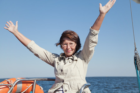 yachtsman: Elderly woman yachtsman on a sailing yacht shows delight at sunny day