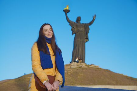 national colors: Young girl dressed in Ukrainian national colors standing on the blue sky background of monument to liberators and smiling happily at autumn sunny day